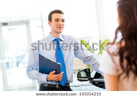 sales manager at a showroom car is worth to the buyer - stock photo