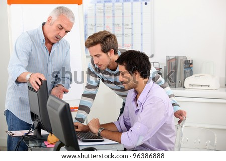 Sales manager demonstrating a point on a computer - stock photo