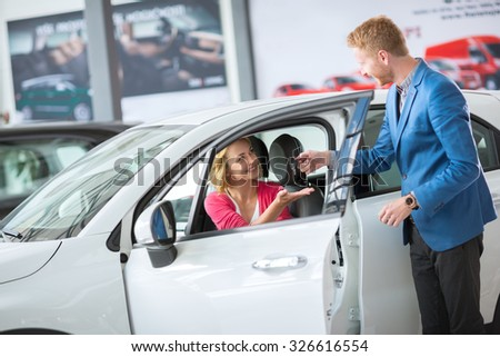 Sales manager giving key from the new car female client  - stock photo