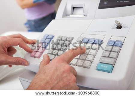 Sales person entering amount on cash register in retail store