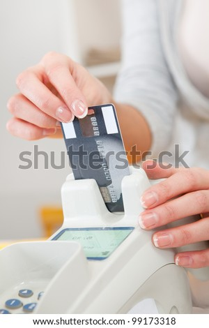 Sales person inserting credit card into scanner - stock photo