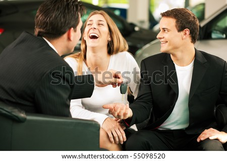Sales situation in a car dealership, the dealer is handing auto keys to a young couple, they are excited, cars standing in the background - stock photo