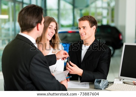 Sales situation in a car dealership, the young couple gets the key for the new car - stock photo