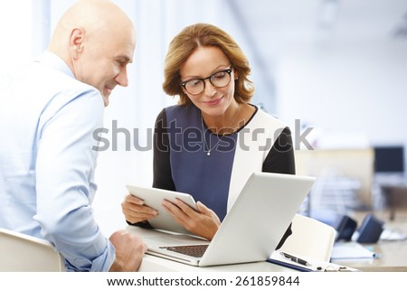 Sales team consulting while sitting at office and using laptop and digital tablet.  - stock photo