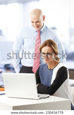 Sales team with laptop analyzing financial datas while sitting at office.  - stock photo