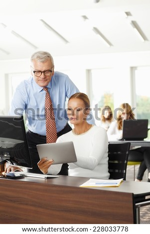 Sales woman holding tablet and discussing problems with senior businessman.