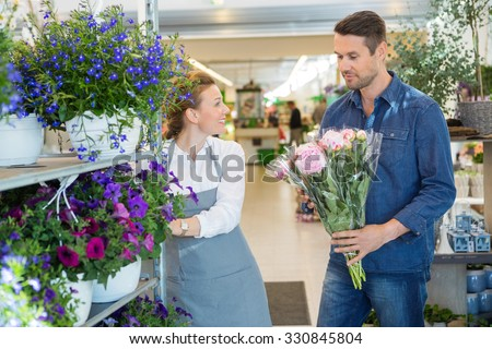 Salesgirl assisting male customer in buying flower bouquet at store - stock photo