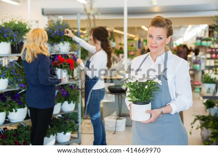 Salesgirl Holding Flower Pot In Florist Shop - stock photo