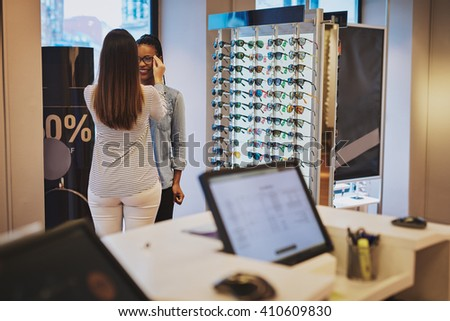 Saleslady assisting a customer in a store trying on eyeglasses with a view of a computer terminal in the foreground