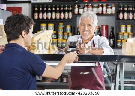 Salesman Accepting Mobile Payment From Customer In Cheese Shop