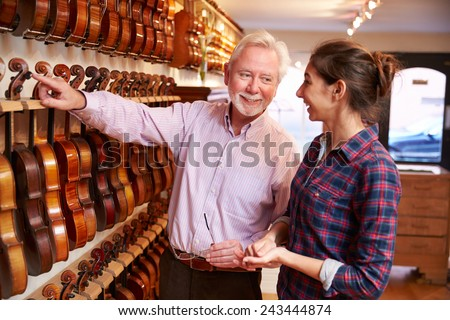 Salesman Advising Customer Buying Violin - stock photo