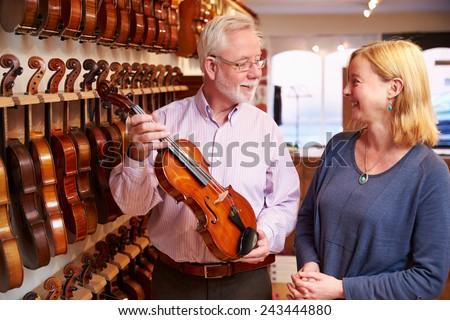 Salesman Advising Customer Buying Violin - stock photo