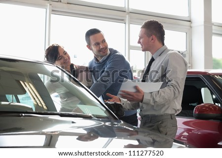Salesman and a couple looking at a car in a car shop - stock photo