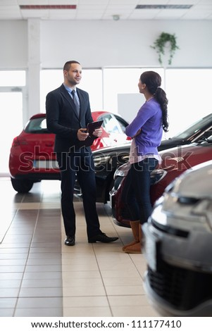 Salesman and a woman talking next to a car in a car shop - stock photo