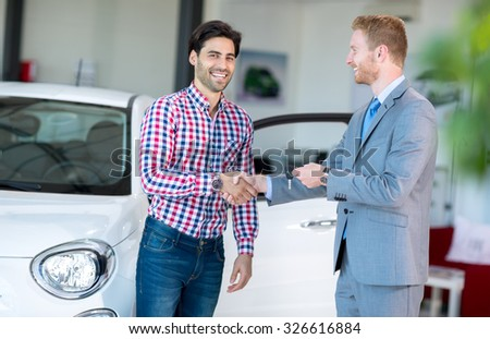 salesman and client at the car saloon, sitting, gesturing and presenting selling conditions - stock photo