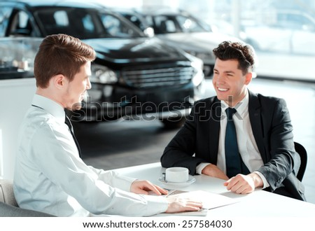 Salesman and customer. Side view of a handsome sales man in car dealership showing corporate booklets to the client while drinking coffee - stock photo