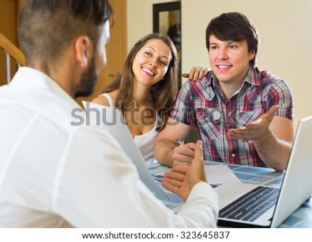 Salesman and positive young couple talking about purchase at their home