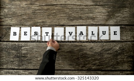 Salesman assembling a Best value sign with white cards over a textured rustic wooden desk.  - stock photo