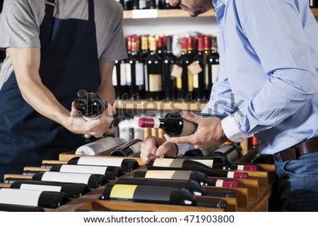 Salesman Assisting Customer In Selecting Wine Bottle At Supermar
