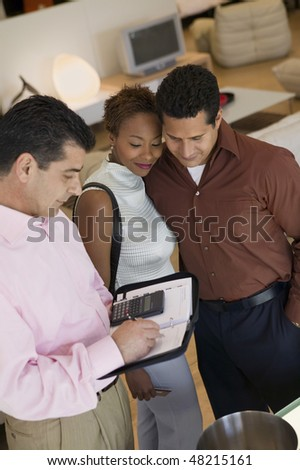 Salesman Calculating Couple's Purchase Amount - stock photo