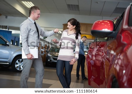 Salesman giving car keys to a woman in a car shop - stock photo