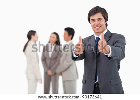 Salesman giving his approval with team behind him against a white background