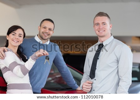 Salesman giving keys to an embracing couple in a car shop - stock photo