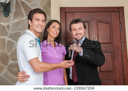 Salesman giving keys to property owners. businessman near entrance door with young couple outside - stock photo