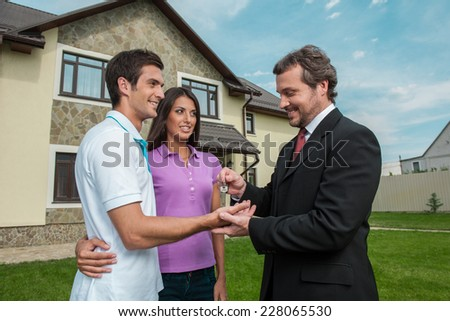 Salesman giving keys to property owners. real estate agent signed deal with young couple outside - stock photo