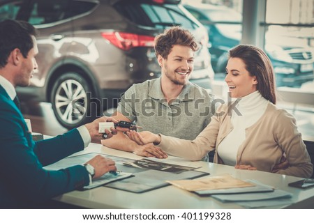 Salesman giving the key of the new car to a young couple at the dealership showroom. - stock photo
