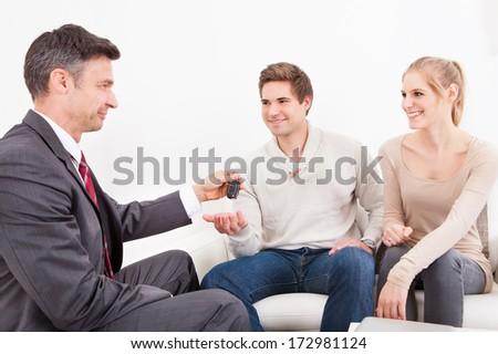 Salesman Handing Car Key To Happy Young Couple - stock photo