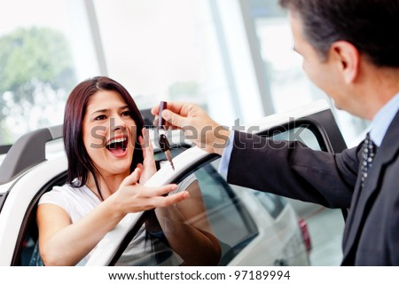 Salesman handling keys to a woman after buying a car - stock photo