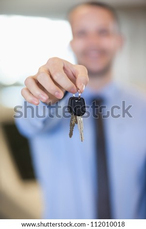 Salesman holding car keys by his fingertips in a dealership - stock photo