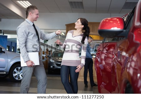 Salesman holding paper and giving keys to a woman in a car shop - stock photo