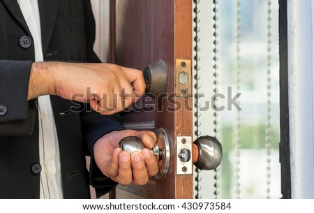 salesman in black suit open the door by key for welcome customer and blur curtain background  - can use to display or montage product - stock photo