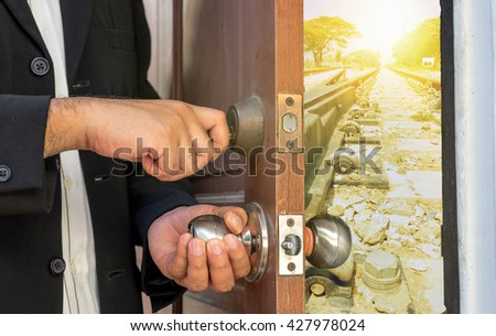 salesman in black suit open the door by key to train railway - can use to display or montage product or concept open your mind - stock photo