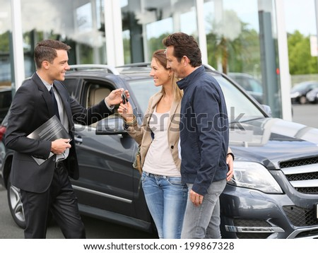 Salesman in car dealership giving keys to clients - stock photo