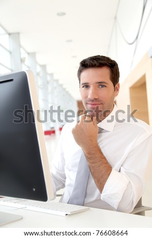 Salesman in front of desktop computer - stock photo