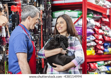 Salesman Looking At Customer With Bulldog In Pet Store - stock photo