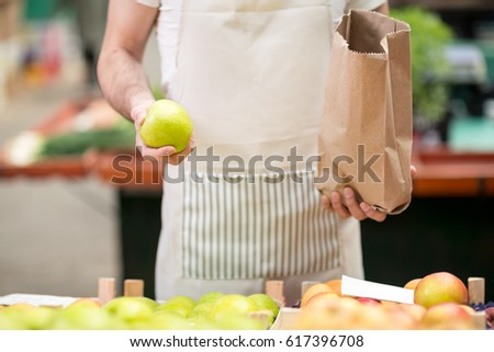 salesman offers an apple at market store