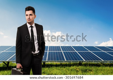 Salesman or businessman holding briefcase on solar power panels background. Manager of sun energy company - stock photo