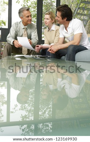 Salesman or investment advisor sitting with clients giving a presentation at the end of a reflective glass topped table