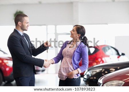 Salesman shaking the hand of a woman and giving her car keys in a car shop