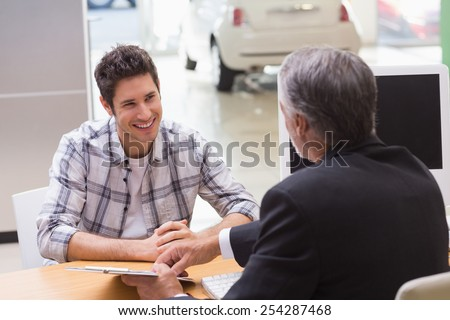 Salesman showing client where to sign the deal at new car showroom - stock photo