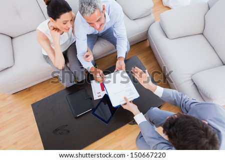 Salesman showing contract to couple who are about to sign at home on couch - stock photo