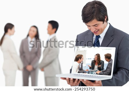 Salesman showing laptop screen with team behind him against attractive businesswoman laughing with her team - stock photo