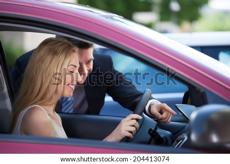 Salesman showing new car to female customer - stock photo