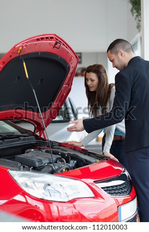 Salesman showing the car engine in a garage