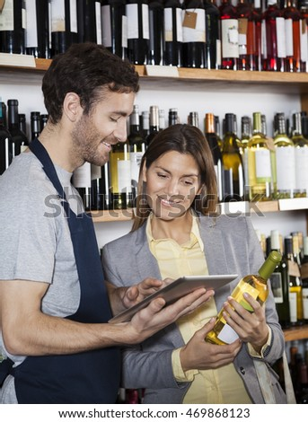 Salesman Showing Wine Information To Customer On Digital Tablet
