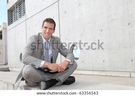 Salesman sitting cross-legged in front of building